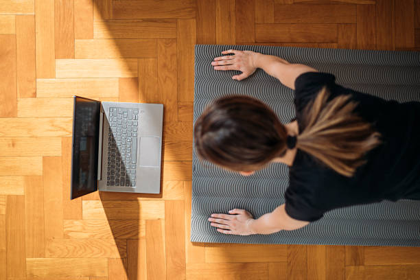 girl doing push-ups at home and watching exercises on laptop stock photo