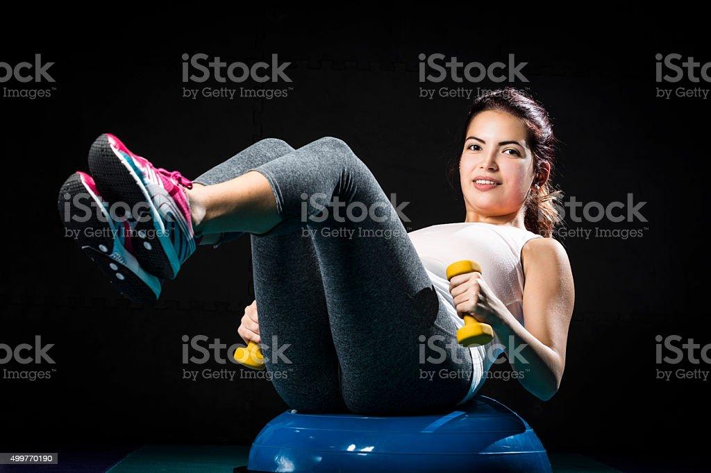 Girl doing sit-ups holding dumbbells sitting on bosu balance ball stock photo