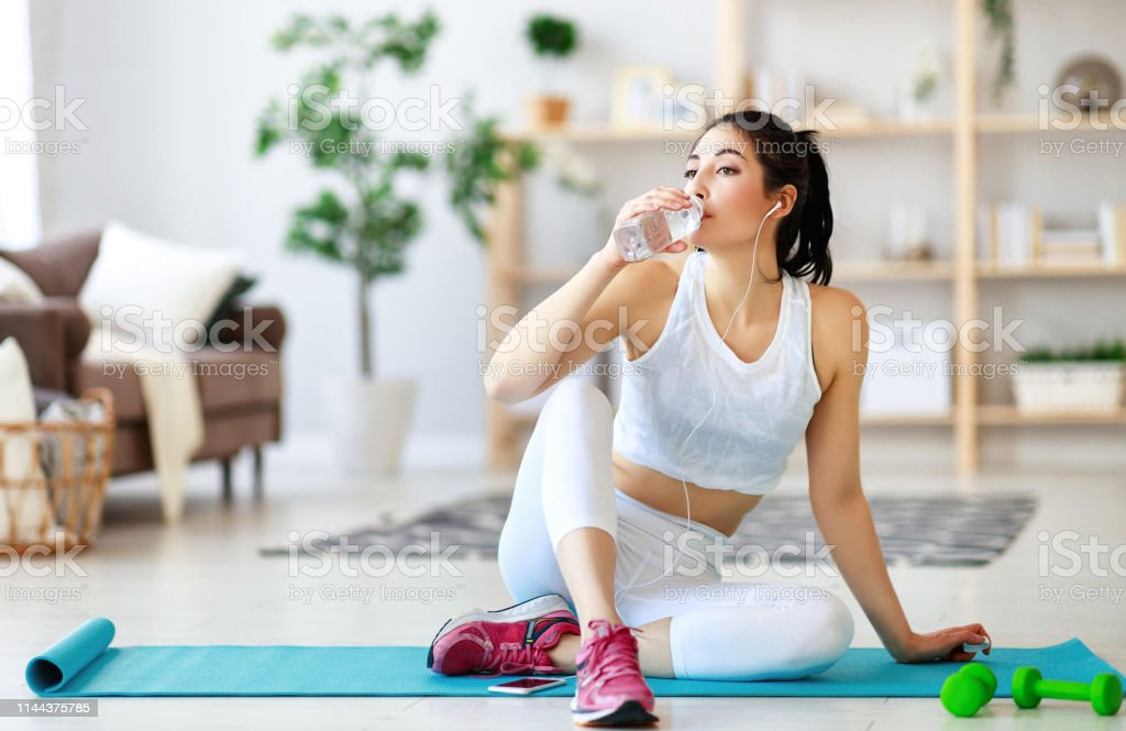 a girl doing sports fitness at home resting and drinking water