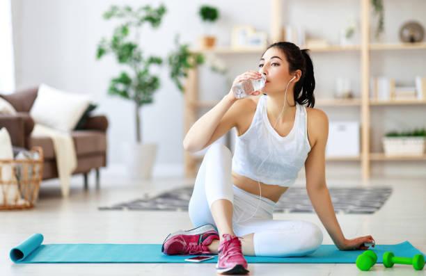meisje doet sport fitness thuis rusten en drinkwater - atlete stockfoto's en -beelden