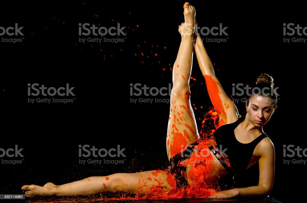 Girl doing stretching bathed in orange paint stock photo