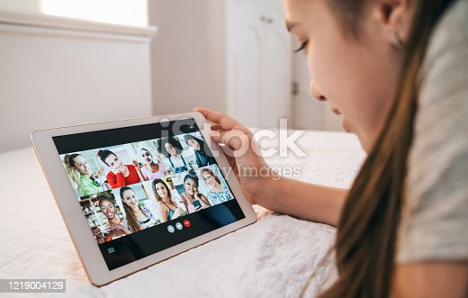Girl doing teleconferencing while using tablet at home during isolation