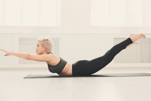 Girl doing warming up exercise for spine, backbend Girl doing warming up exercise for spine, backbend, arching stretching her back working out at yoga class, copy space bending stock pictures, royalty-free photos & images