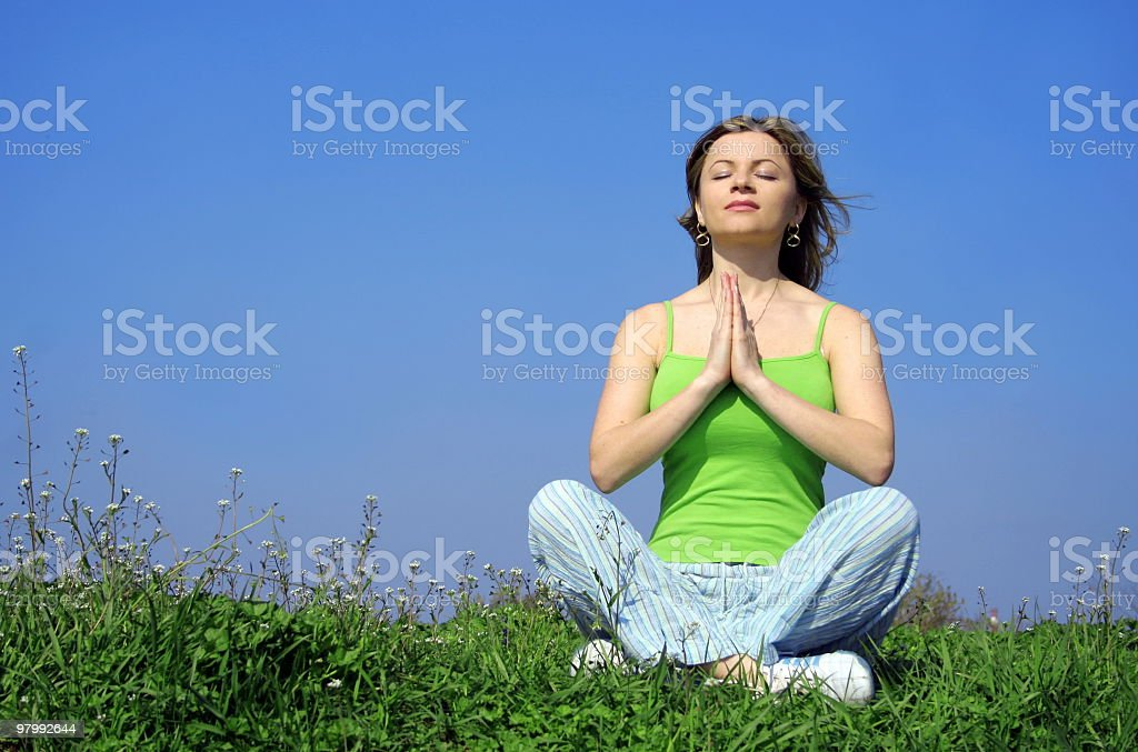 Girl doing yoga against blue sky royalty-free stock photo