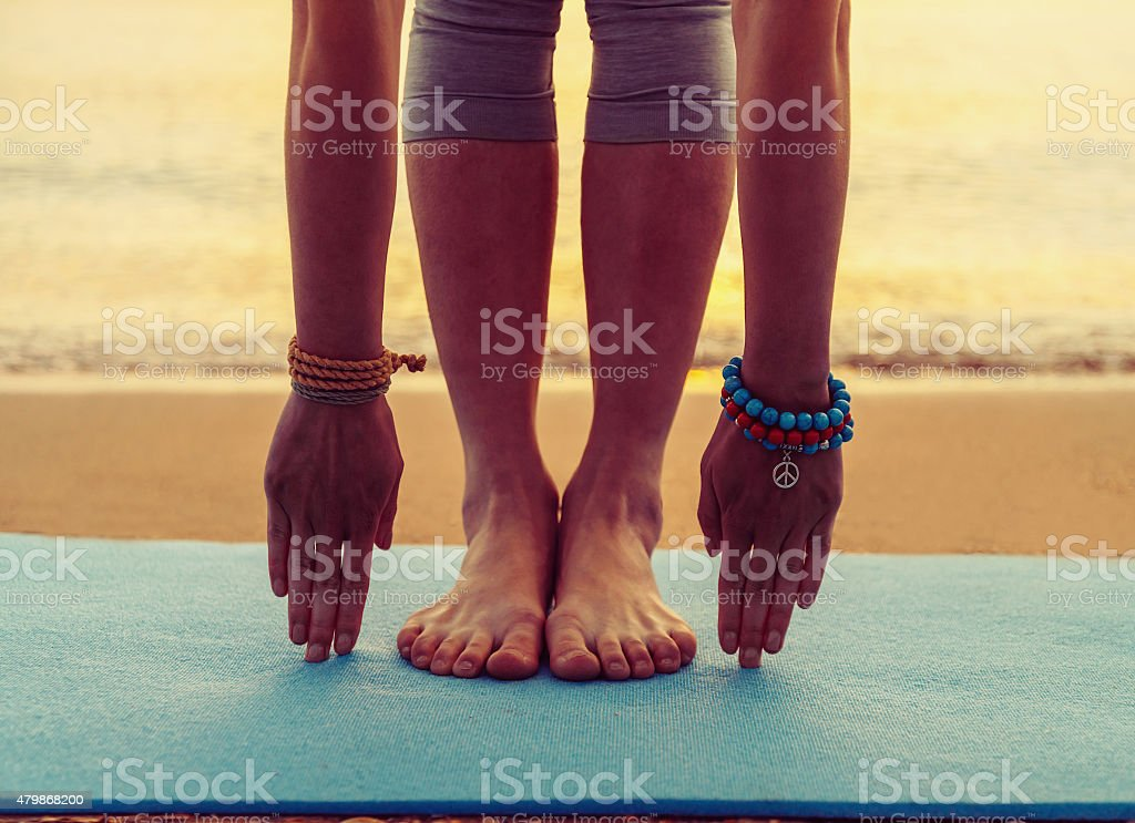 Girl doing yoga exercise on beach Young woman doing yoga exercise on beach near the sea at sunset in summer, face is not visible 2015 Stock Photo