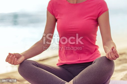 Cropped image of beautiful girl in sport clothes meditating while sitting in lotus position on the beach