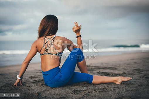 istock Girl doing yoga on the beach 961139614
