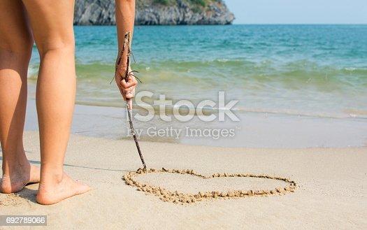 Girl drawing a hearth shape on a sandy beach
