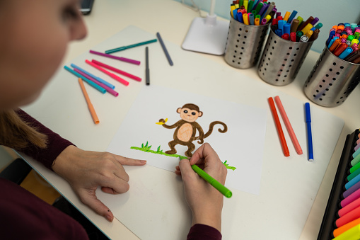 818512928 istock photo Girl drawing a monkey 1203980958