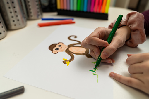 818512928 istock photo Girl drawing a monkey 1203981013