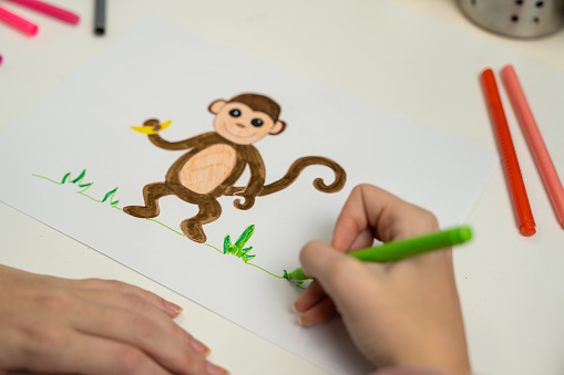 818512928 istock photo Girl drawing a monkey 1203982002
