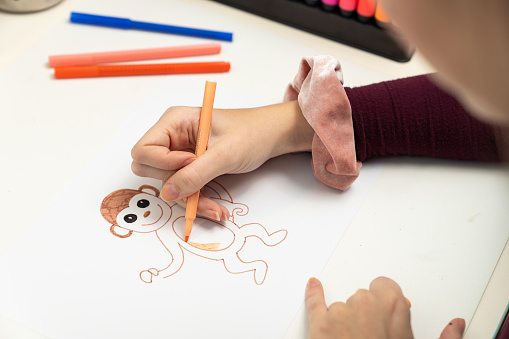 818512928 istock photo Girl drawing a monkey 1203982128