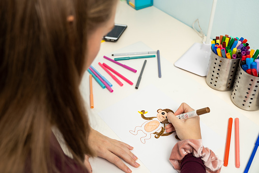 818512928 istock photo Girl drawing a monkey 1203982450