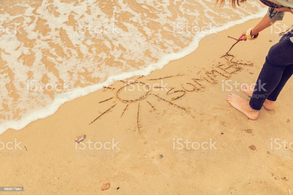 Girl drawing a sun in the sand of ocean / sea beach. royalty-free stock photo