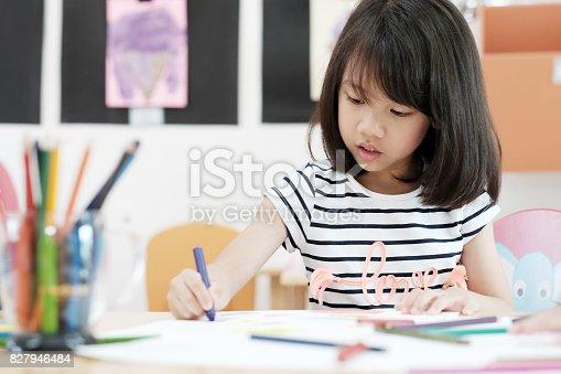 istock Girl drawing color pencils in kindergarten classroom, preschool and kid education concept 827946484
