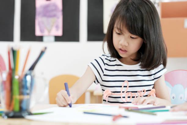mädchen zeichnung farbstiften im kindergarten klassenraum, vorschule und kind bildungskonzept - zeichnen lernen mit bleistift stock-fotos und bilder