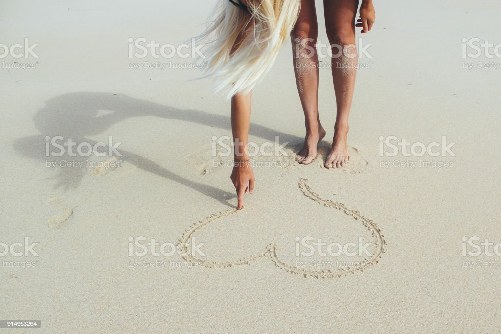 Girl drawing heart shape into the sand stock photo