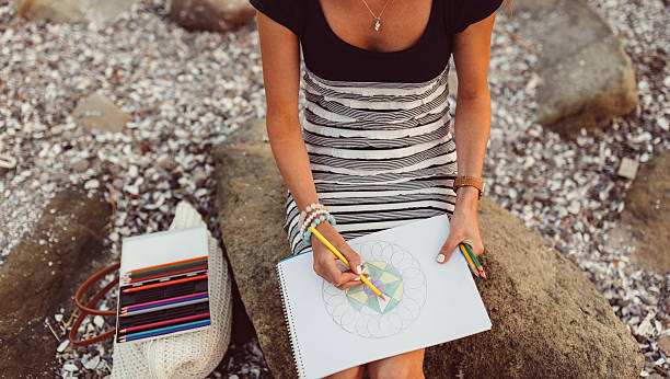 Girl drawing in coloring book stock photo