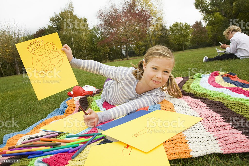 Girl drawing on picnic blanket royalty-free stock photo