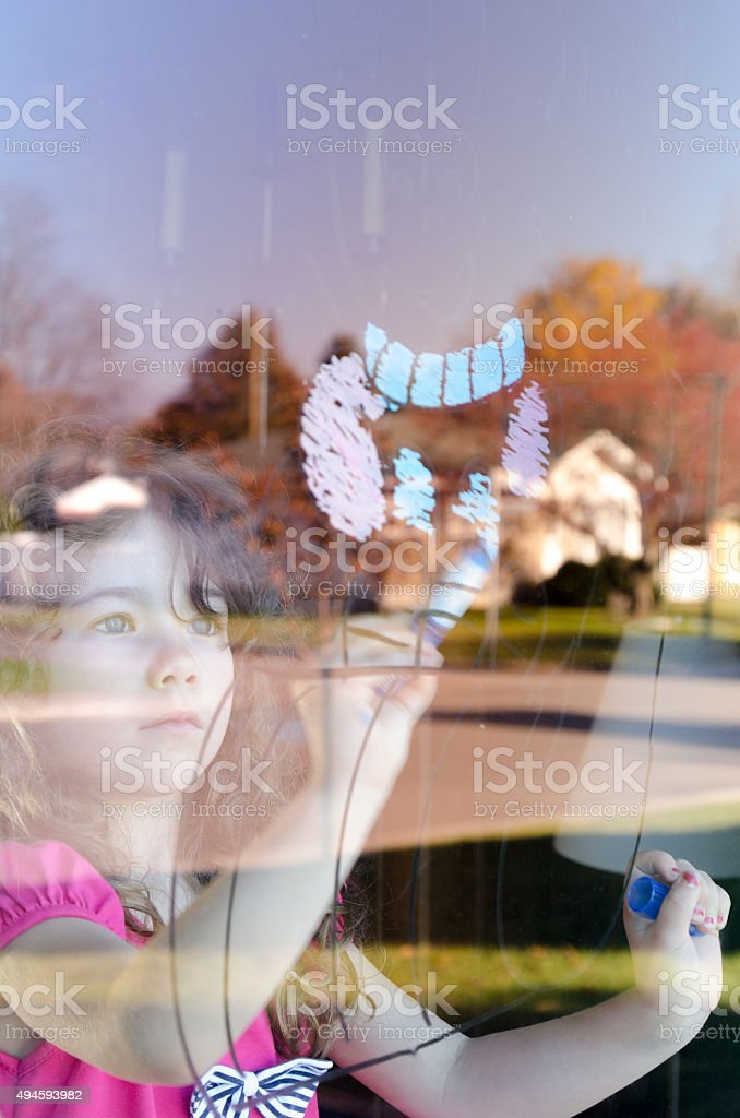 Girl drawing on the window of the living room stock photo