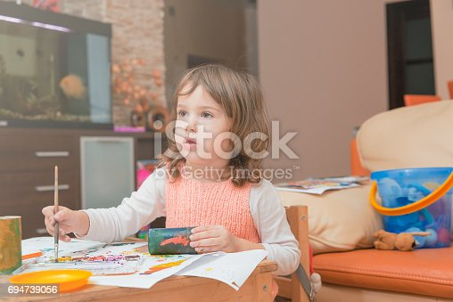 istock girl drawing paints on paper and hands 694739056