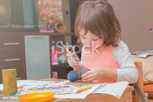 istock girl drawing paints on paper and hands 694739092
