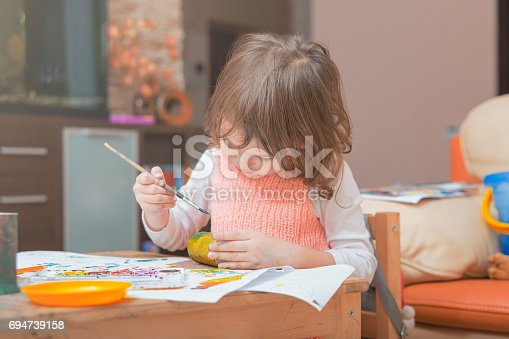 istock girl drawing paints on paper and hands 694739158