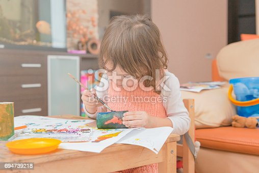 istock girl drawing paints on paper and hands 694739218