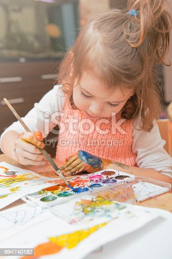 istock girl drawing paints on paper and hands 694740182