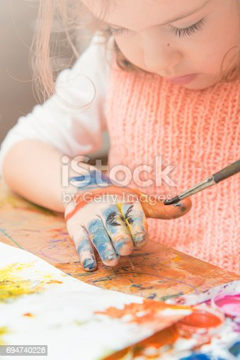 istock girl drawing paints on paper and hands 694740228
