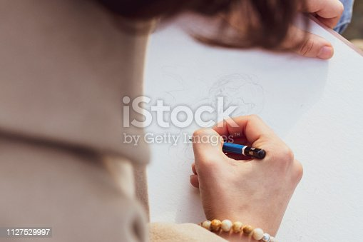 istock Girl drawing with Pencil 1127529997