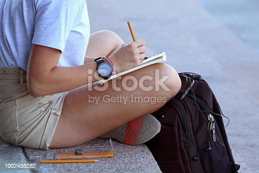 818512928istockphoto girl draws in a notebook sitting on the pavement 1002435282