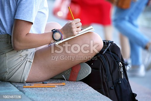818512928istockphoto girl draws in a notebook sitting on the pavement 1002457226