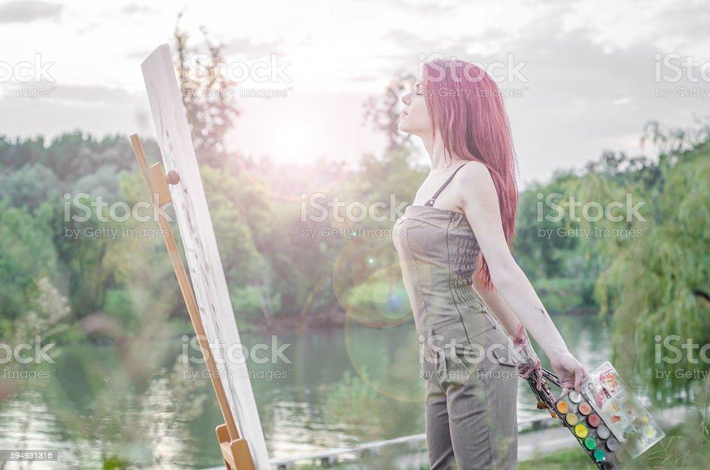Girl draws nature, painter posing and enjoys stock photo