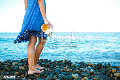 Young girl holding a sea conch at the beach.