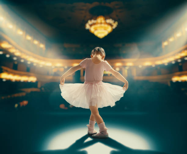 girl dreaming of becoming a ballerina Cute little girl dreaming of becoming a ballerina. Child girl in a pink tutu dancing on the stage. Baby girl is studying ballet. performing arts event stock pictures, royalty-free photos & images