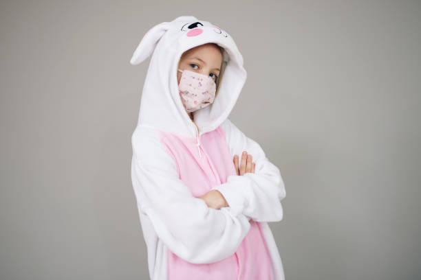 girl dressed as easter bunny rabbit with face mask stock photo