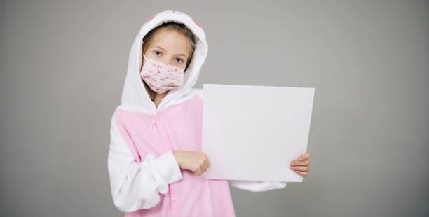 Mädchen als Osterhase mit Gesicht Schutzmaske halten weißes Brett gekleidet – Foto