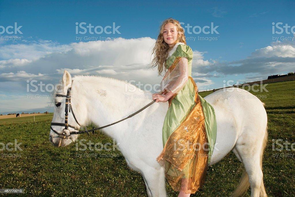 Girl dressed as princess riding horse stock photo