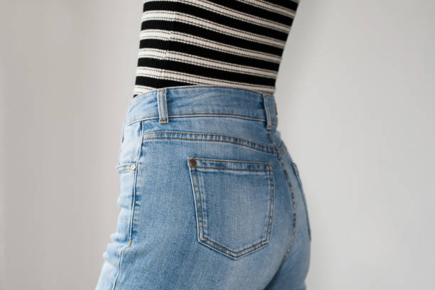 Girl dressed blue jeans and striped t-shirt, side view. Copy space. White background. Girl dressed blue jeans and striped t-shirt, side view. Copy space. White background. skinny jeans stock pictures, royalty-free photos & images