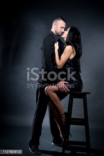 istock Girl dressed in black dress kissing and hug her big boss 1127829122