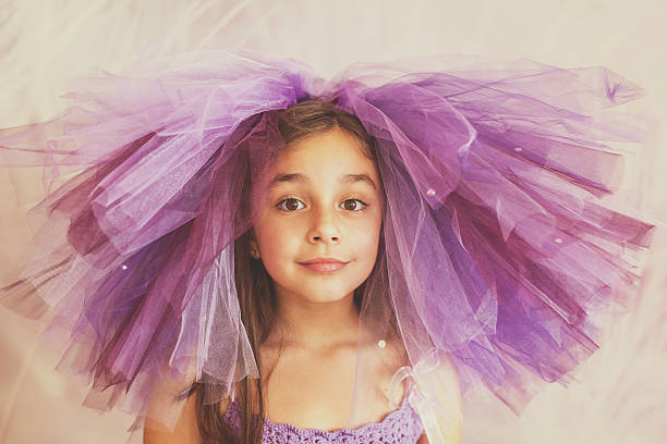mädchen, gekleidet in lila mit einer lustigen hut - prinzessinnen tutu stock-fotos und bilder