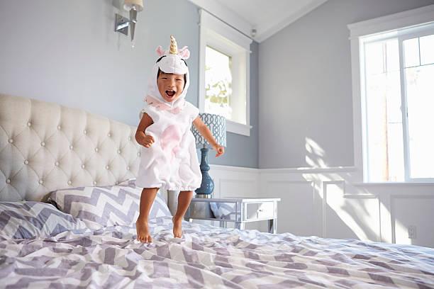 vestido menina na fantasia de unicórnio saltar na cama em casa - unicorn bed imagens e fotografias de stock