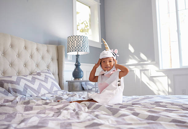 vestido menina na fantasia de unicórnio sentado sobre cama em casa - unicorn bed imagens e fotografias de stock