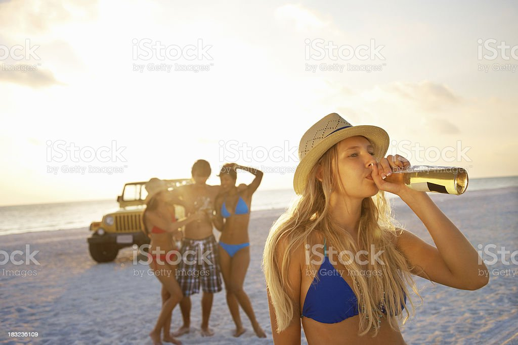 Girl drinking beer and her friends in background on beach royalty-free stock photo