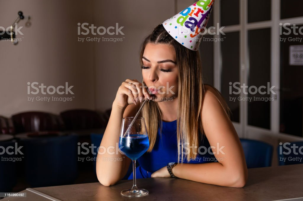 Young girl drinking cocktail blue lagoon at the empty bar with...