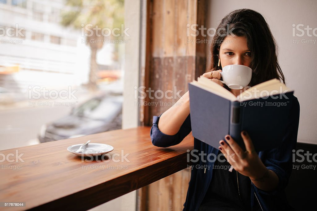 Girl Drinking Coffee and Reading Book in Cafe stock photo