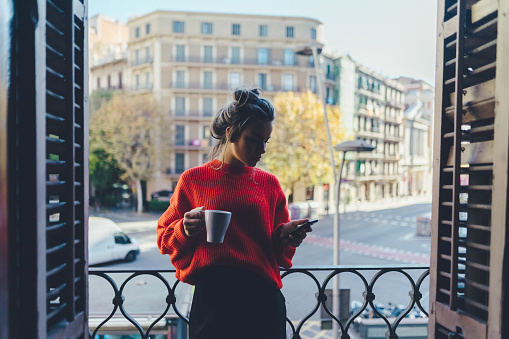 Girl drinking coffee at the balcony in Barcelona