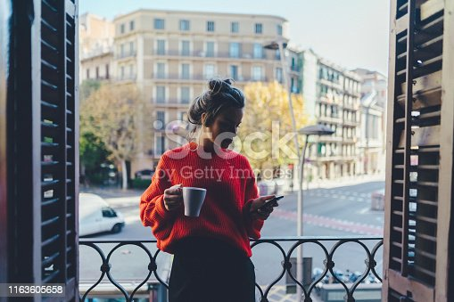 Young woman relaxing at the terrace and drinking coffee
