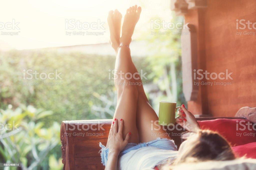Girl drinking coffee / tea and enjoying the sunrise / sunset in garden. stock photo